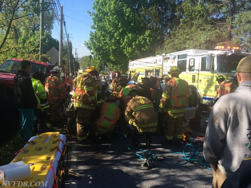 Firefighters work to extricate a victim at today's crash.