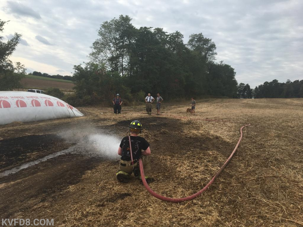 Firefighters wetting down the field after the fire was extinguished.