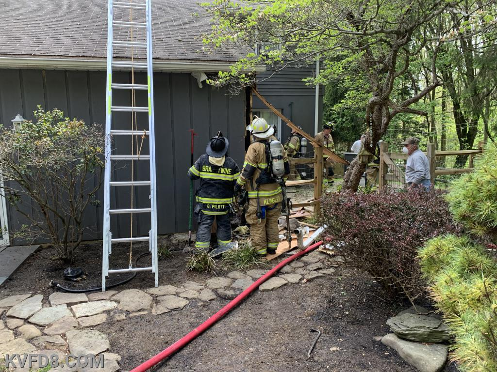 Firefighters extinguish a small fire in the back wall of the home.