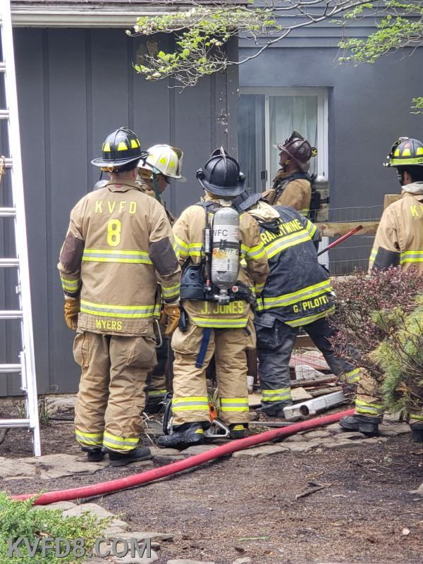 Firefighters extinguish a small fire in the back wall of the home. Photo by George Degman